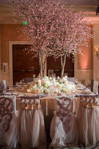 pink-flowers-on-tree-branch-centerpiece-at-tamra-barneys-wedding