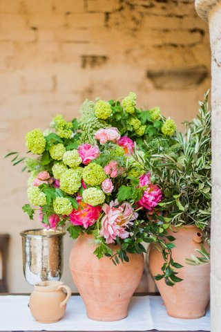 wedding-reception-in-historic-venue-courtyard-italy-terracotta-vase-green-flowers-pink-peony-blooms