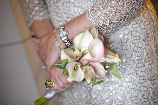 mother-of-the-bride-at-wedding-in-a-long-sleeve-sequined-dress-holds-white-calla-lily-bouquet