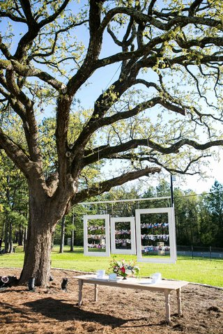 large-tree-at-outdoor-wedding-suspending-white-frames-with-family-photos-above-guest-book-table