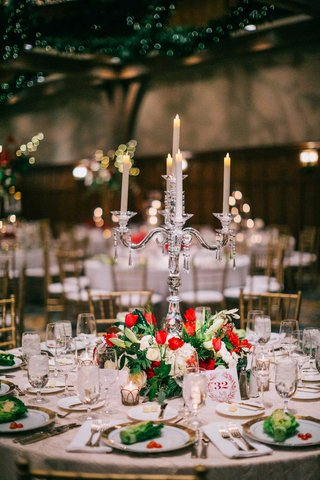 low-centerpiece-of-white-red-flowers-greenery-with-crystal-candelabra-lettuce-on-plates