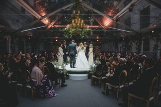 wedding-ceremony-moody-lighting-jewish-traditions-stage-in-the-round-clear-tent-chandelier-greenery
