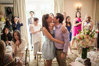 bride-to-be-in-oscar-de-la-renta-cocktail-dress-kisses-groom-at-bridal-shower