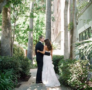 groom-in-a-black-tuxedo-bride-in-a-strapless-alencon-lace-gown-in-garden-at-jonathan-club