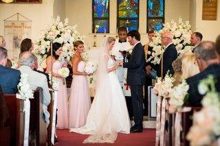 bride-in-carolina-herrera-dress-puts-ring-on-groom-at-church-wedding-ceremony-in-the-bahamas