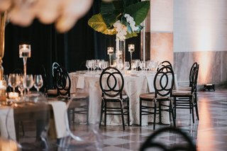 wedding-reception-checkerboard-flooring-black-chairs-white-marble-linen-greenery-tropical-leaves