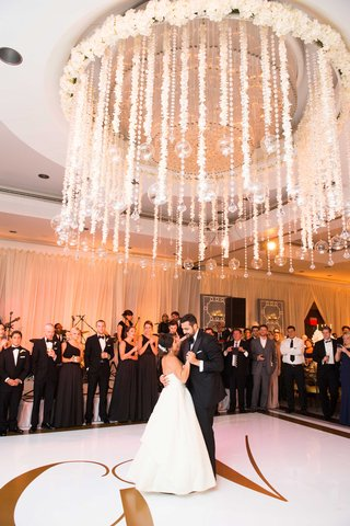 bride-in-strapless-wedding-dress-and-groom-in-tuxedo-share-first-dance-under-flowers-and-crystals