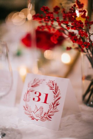 wedding-reception-holiday-theme-red-wreath-dove-table-number-on-white-linen-red-foliage-winter