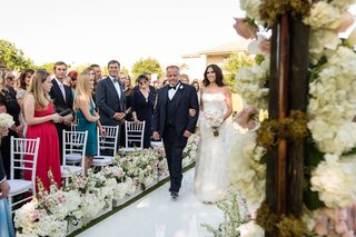 bride-walking-down-aisle-with-father-of-bride-white-boxes-along-aisle-with-white-hydrangeas-and-rose