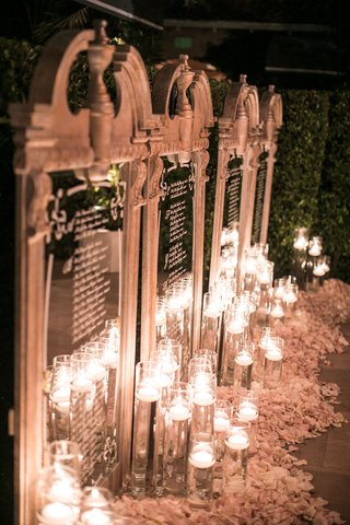 wedding-reception-seating-chart-mirror-illuminated-with-floating-candles-flower-petals-calligraphy