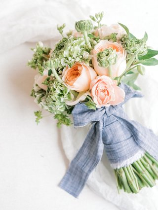wedding-event-bridal-shower-bouquet-peach-roses-greenery-blue-linen-tied-into-bow-around-arrangement