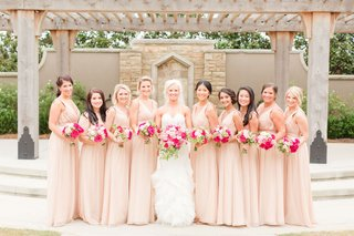 bride-in-strapless-wedding-dress-big-pink-bouquet-bridesmaids-in-long-v-neck-dresses-in-pale-pink