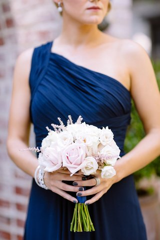 bridesmaid-in-a-one-shoulder-dark-blue-monique-lhuillier-dress-with-bouquet-of-pearl-and-blush-roses