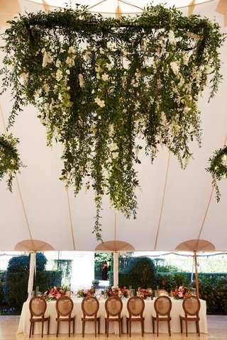 wedding-reception-tent-long-table-wood-chairs-low-centerpiece-floral-chandelier-greenery