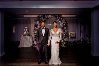 bride-in-long-sleeve-lace-sheath-dress-groom-in-tuxedo-newlyweds-in-front-of-floral-arch