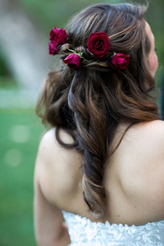 bride-in-strapless-wedding-dress-with-curled-brunette-locks-and-deep-burgundy-roses-in-hairstyle