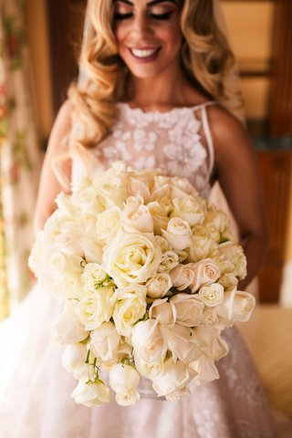 bride-holding-bouquet-of-white-cream-rose-flowers-semi-cascading-design-high-neck-bridal-gown