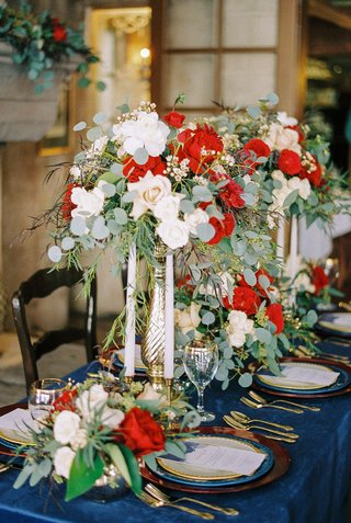 beauty-beast-movie-styled-wedding-shoot-silver-vases-red-white-flowers-foliage-candles-blue-linen