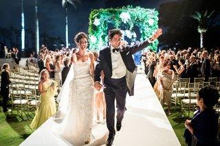 wedding-couple-on-raised-aisle-walking-hand-in-hand-up-aisle-husband-wife-lighting-night-ceremony