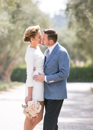 bride-in-white-mini-dress-and-groom-in-casual-blue-jacket-kiss