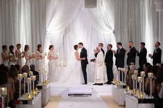 bridal-party-applauds-during-bride-and-grooms-first-kiss-white-wedding-ceremony-altar