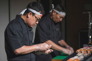 sushi-servers-dressed-in-black-make-sushi-at-a-wedding-reception-food-station