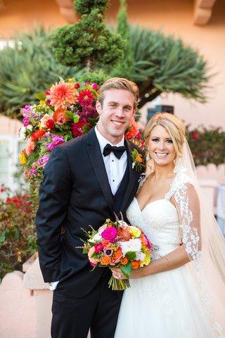 newlyweds-posing-colorful-vibrant-bouquet-la-jolla-wedding-veil-tuxedo-la-valenica-hotel-cute-couple