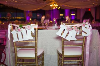gold-chairs-decorated-with-mr-and-mrs-and-flowers