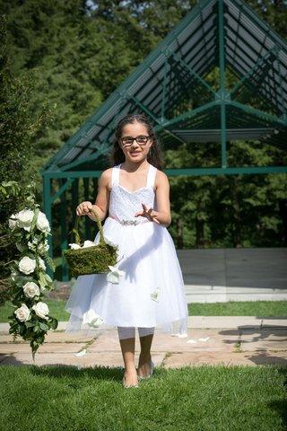 flower-girl-in-white-tank-dress-tossing-flower-petals-moss-basket-green-lawn-glasses