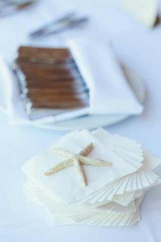 seaside-wedding-reception-with-stack-of-napkins-weighed-down-by-a-starfish