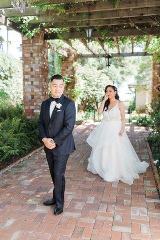 wedding-in-santa-barbara-terrace-brick-flooring-first-look-bride-crying-holding-up-hand