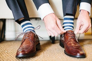 groom-wearing-blue-and-white-stripe-socks-with-brown-lace-up-wingtip-dress-shoes