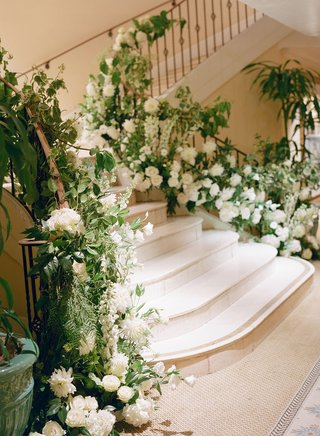 stairs-to-wedding-reception-ballroom-decorated-with-fresh-greenery-and-white-flowers-dahlias-roses