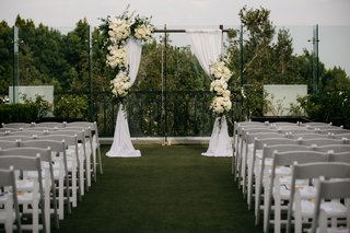 rooftop-wedding-simple-arch-with-white-drapery-and-ivory-flowers