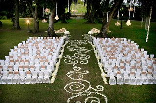 white-chair-covers-on-ceremony-lawn-with-flower-petal-aisle
