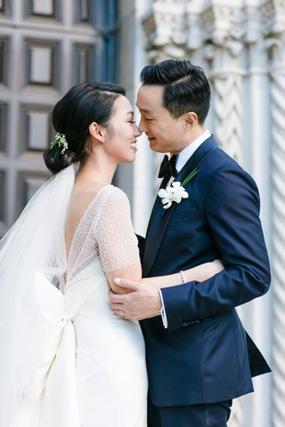 bride-with-low-bun-and-veil-below-with-pretty-bow-dress-and-ceremony-top-groom-in-navy-blue-suit