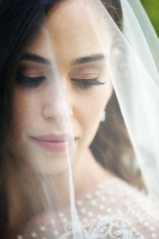 close-up-of-bride-behind-veil-long-eyelashes-neutral-makeup-pink-lip-blush-freckles-sabrina-dahan