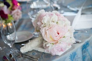 brides-bouquet-of-white-and-pink-peonies-wrapped-in-fabric-with-floral-appliques