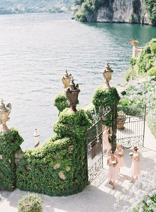 bridesmaids-and-flower-girls-walking-up-boat-dock-to-entrance-of-villa-del-balbianello-lake-como