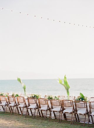 wedding-tablescape-with-ocean-view-string-lights-rattan-wood-chairs-white-cushions-green-palm-leaf