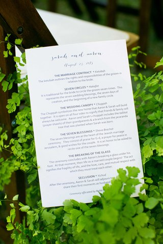 a-couples-ceremony-program-for-tradition-jewish-wedding-sitting-amongst-green-foliage