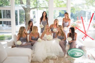 bride-in-vera-wang-wedding-dress-with-bridesmaids-in-light-grey-dresses-on-white-couch-at-home