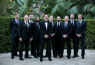 groom-wearing-tuxedo-and-bow-tie-and-groomsmen-wearing-black-suits-and-ties