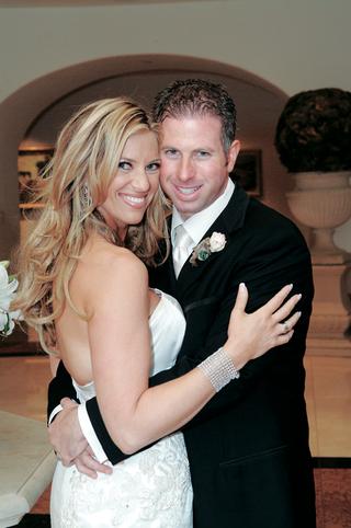 groom-embraces-bride-in-wedding-photo
