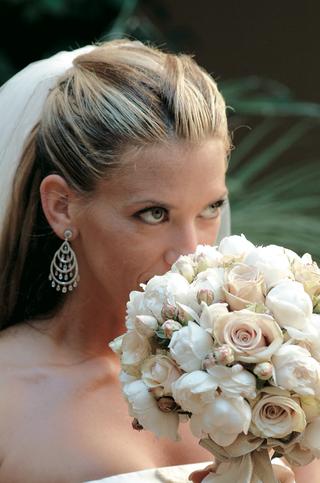 bride-wearing-earring-smells-flower-bouquet