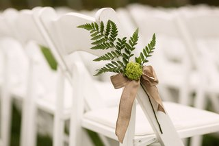green-fern-tied-to-white-ceremony-chair-with-brown-ribbon-outdoor-vineyard-wedding