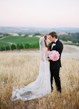 bride-and-groom-kissing-at-family-vineyard