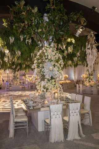 wedding-reception-ballroom-square-mirror-tablee-draped-chairs-white-flowers-greenery-over-chandelier