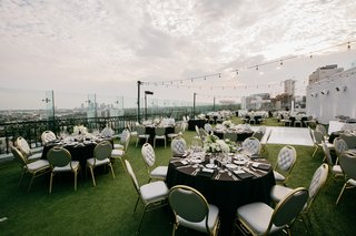 rooftop-wedding-reception-grey-chairs-with-gold-bistro-lights-astroturf