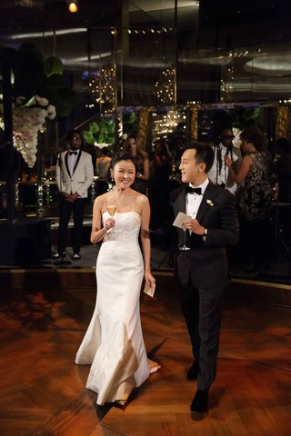 bride-and-groom-tuxedo-and-strapless-wedding-dress-holding-champagne-glasses-in-front-of-band-stage